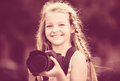 Cheerful female child taking pictures with camera in park