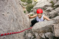 Cheerful female climber ascending a rock Stock Photography