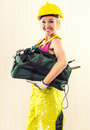 Cheerful female construction worker smiling with tool bag posing indoors Royalty Free Stock Images
