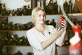 Cheerful female customer picking red glazed crockery Royalty Free Stock Photo