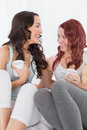 Cheerful female friends chatting over coffee in bed relaxed at home Royalty Free Stock Photography