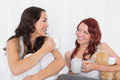 Cheerful female friends chatting over coffee in bed young at home Stock Image