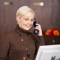 Cheerful female receptionist using telephone portrait of a Stock Photo