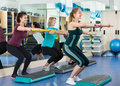Cheerful females working out on aerobic step platform Royalty Free Stock Photo