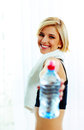 Cheerful fit woman passing a bottle of water to you young Royalty Free Stock Photography
