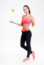 Cheerful fitness woman throwing an apple and showing thumbs up full length of attractive young in pink top black leggings Royalty Free Stock Photography