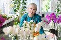 Cheerful florist portrait of beautiful with orchids in the flower centr Royalty Free Stock Images