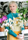 Cheerful florist portrait of beautiful with orchids in the flower centr Royalty Free Stock Photos