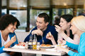 Cheerful friends chatting while lunch four in restaurant Stock Images