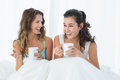 Cheerful friends with coffee cups chatting in bed young female at home Royalty Free Stock Photos