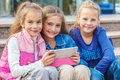 Cheerful friends with an electronic tablet sitting in the outdoor Stock Photos