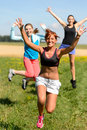 Cheerful friends jumping enjoy summer sport run running sunny meadow Stock Image