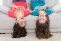 Cheerful friends lying upside down on sofa at home two young female in living room Stock Images