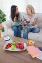 Cheerful friends playing video games and laughing at home on couch Stock Photos