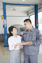 Cheerful garage mechanic explaining to customer and showing her the bill Stock Image