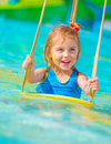 Cheerful girl in aqua park closeup on baby with face paint swinging on water attractions having fun poolside summer vacation happy Stock Photo