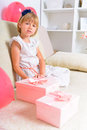 Cheerful girl with birthday gifts little sittig on the couch Stock Photography