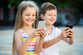 Cheerful girl and boy looking at mobile phones in park Royalty Free Stock Photo