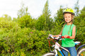Cheerful girl with braids in helmet holds bike blond bicycle the forest summer Royalty Free Stock Images