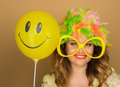Cheerful girl in a bright wig and big glasses holding a balloon on the background Stock Images