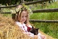 Cheerful girl with a cat sitting on haystack Royalty Free Stock Photo