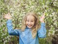 A cheerful girl in a denim shirt raised her hands up in the cherry orchard. Royalty Free Stock Photo