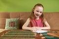 Cheerful girl in dress draws pencils