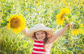 Cheerful girl with hat among sunflowers Royalty Free Stock Photo