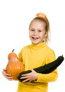 Cheerful girl holding a pumpkin and squash Royalty Free Stock Photo