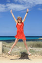 Cheerful girl jumping on the beach and opens her mouth Stock Photos