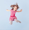Cheerful girl jumping on a blue background Stock Image