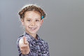 Cheerful girl lifts thumb upwards little on gray background Royalty Free Stock Image