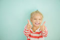 Cheerful girl lifts thumb upwards little on green background Royalty Free Stock Photo