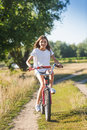 Cheerful girl with long hair riding her bicycle on dirt road at Royalty Free Stock Photo