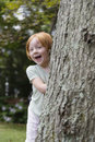 Cheerful girl peeking from behind tree portrait of a little Stock Photography