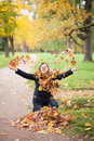 Cheerful girl playing with autumn leaves Royalty Free Stock Photography