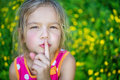 Cheerful girl puts index finger to lips little for silence on green background Royalty Free Stock Images