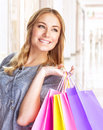 Cheerful girl with shopping bags closeup portrait of sweet standing in big centre colourful paper doing purchase pleasure Royalty Free Stock Image