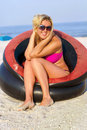 Cheerful girl sitting in an inflatable chair on the beach Stock Photography