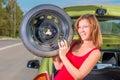 Cheerful girl with a spare wheel near the car Stock Photo