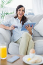 Cheerful gorgeous brunette buying online having breakfast in her living room Stock Photos