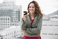 Cheerful gorgeous brunette in winter fashion holding smartphone on urban background Stock Photography