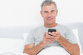 Cheerful grey haired man sending a text in bed smiling at camera bedroom at home Stock Photos