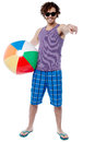 Cheerful guy with beach ball pointing at you relaxed young man enjoying vacation Stock Photo