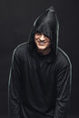 Cheerful guy in a black robe the dark Stock Photography