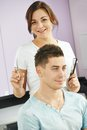 Cheerful hairdresser in beauty salon female with scissors and comb with men client parlour Stock Photography