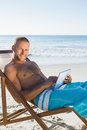 Cheerful handsome man using his tablet while sunbathing Royalty Free Stock Photo