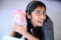 Cheerful Indian girl holding Piggybank Stock Photo