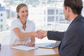 Cheerful interviewer shaking hand of an interviewee during a job interview Stock Photos