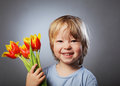 Cheerful kid with a bouquet of tulips Royalty Free Stock Photos